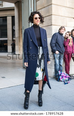 PARIS - FEBRUARY 26, 2014: Stylish European woman with sunglasses, blue coat at the Place Vendome. Paris Fashion Week: Ready to Wear 2014/2015 is held in Paris from February 25 to March 5, 2014. - stock photo