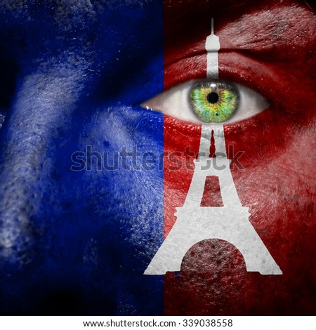 Paris flag with Eiffel tower painted on a mans face to support the people of Paris - stock photo