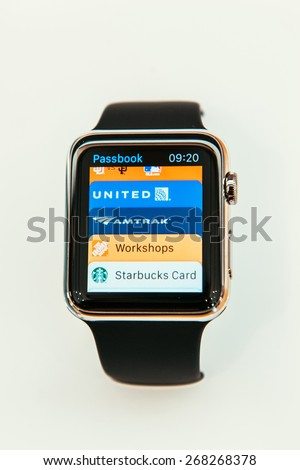PARIS, FRANCE  - APR 10, 2015: New wearable computer Apple Watch smartwatch displaying the new Passbook App. Apple Watch has an integration with iOS Apple products and services - stock photo