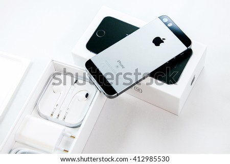 PARIS, FRANCE - APR 21, 2016: Unboxing of the new Apple iPhone SE combining the updated processor, 4K rear camera, touch id, retina display - stock photo
