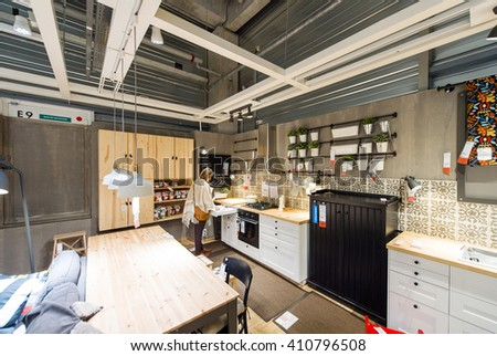 PARIS, FRANCE - APR 12, 2016: Woman choosing modern kitchen furniture and kitchen appliances in the modern IKEA shopping furniture mall in Paris  - stock photo