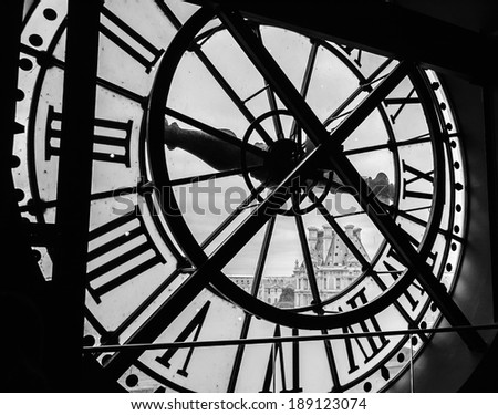 PARIS, FRANCE - APRIL 6, 2014: A clock with roman numerals in the museum D'Orsay and the view on the Louvre museum. Musee d'Orsay has the largest collection of impressionist paintings in the world. - stock photo