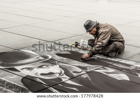 PARIS, FRANCE -  APRIL 26:Artist during drawing Charlie Chaplin on sidewalk near Centre Georges Pompidou on april 26, 2013 in Paris.Many artists show their work near the Centre Georges Pompidou. - stock photo
