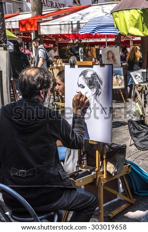 PARIS, FRANCE - APRIL 23, 2015: Artists easels and artwork set up in Place du Tertre in Montmartre. Montmartre attracted many famous modern artists including Picasso and Dali. - stock photo