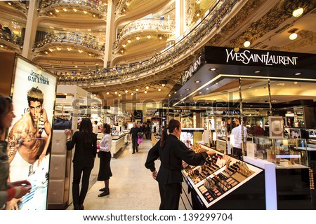 PARIS, FRANCE - APRIL 24 : inside part of the famous Galeries Lafayette with it's brand stands Yves Saint Laurent, Jean Paul Gaultier, Lancome and customers on April 24th 2013 in Paris, France - stock photo
