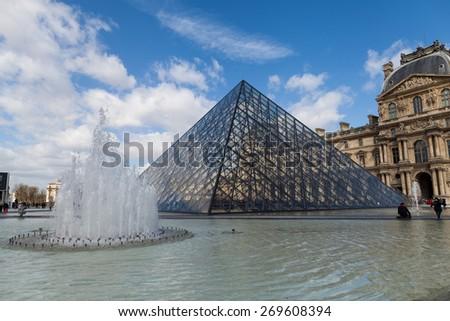 PARIS, FRANCE - APRIL 1, 2015: Louvre Museum with Glass Pyramids, Famous Tourism Landmark on April 1, 2015 in Paris France - stock photo