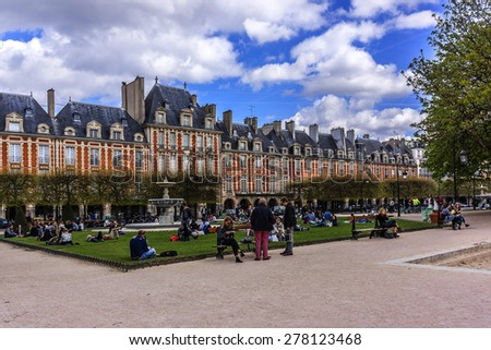 PARIS, FRANCE - APRIL 12, 2015: People relaxing on green lawns of famous Place des Vosges - oldest planned square in Paris, in Marais district. Place des Vosges was built by Henri IV from 1605 to 1612 - stock photo