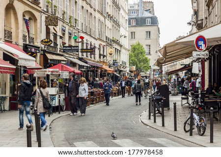 PARIS, FRANCE -  APRIL 26: Tourists walk past a cafeteria and souvenir store on april 26, 2013 in Paris. Paris is the most visited city in the world. - stock photo