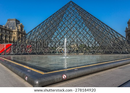 PARIS, FRANCE - APRIL 24, 2015: View of pyramid and fountain at courtyard of Louvre Museum. Louvre Museum is one of the largest and most visited museums worldwide. - stock photo