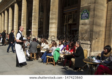 PARIS, FRANCE - APRIL 21 : Waiter serving customers at traditional outdoor Parisian cafe at Place Colette near Louvre on April 21st 2013 in Paris, France  - stock photo