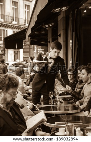 PARIS, FRANCE - APRIL 20, 2014 : Waiter serving customers at traditional outdoor Parisian cafe in center city. - stock photo