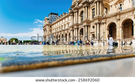 PARIS, FRANCE - AUG 18, 2014: Tourists visiting Louvre - Cour Napoleon in summer with relaxed people sitting on the edge of fountain near the Pyramid by the architect Ieoh Ming Pei. Paris sightseeing - stock photo