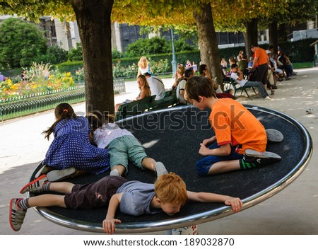 PARIS, FRANCE - AUGUST 14, 2014: Four unidentified children spinning on the carousel in the garden behind Notre Dame de Paris cathedral. Many tourists stay here to rest after visiting the cathedral.  - stock photo