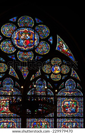 Paris, France - August 11, 2014: Fragment of colorful stained glass window in dark interior of the Notre Dame de Paris cathedral