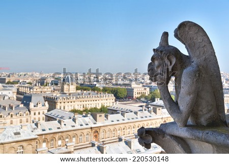 PARIS, FRANCE, August 5, 2014: Notre Dame of Paris: Famous Chimera, demon, overlooking the Eiffel Tower at a summer day