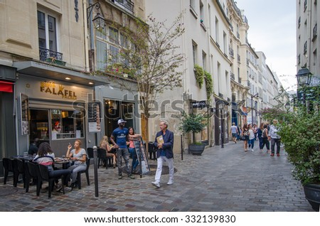 PARIS, FRANCE - AUGUST 31, 2015: People walk past restaurants and shops along Rue des Rosiers in the historic Jewish neighborhood of Marais. - stock photo