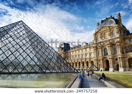 PARIS, FRANCE - AUGUST 13, 2014: The Passage Richelieu and the Pyramid of the Louvre. The Pyramid serves as the main entrance to the Louvre Museum. Paris is popular tourist destination in Europe.