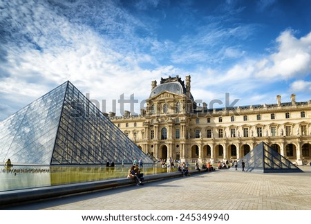 PARIS, FRANCE - AUGUST 13, 2014: The view of the Passage Richelieu and the Pyramid of the Louvre. Paris is one of the most popular tourist destinations in Europe. - stock photo