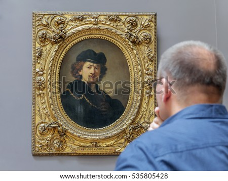 PARIS, FRANCE - AUGUST 28 2013: - Tourist admiring a painting of Rembrandt - Self-Portrait Wearing a Toque and a Gold Chain exhibited at the Louvre Museum, Paris, France