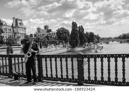 PARIS, FRANCE - AUGUST 14, 2013: Unidentified young saxophone player on the bridge over Seine river near Hotel de Ville (City Hall). Dozens buskers perform on the streets and in the metro of Paris. - stock photo
