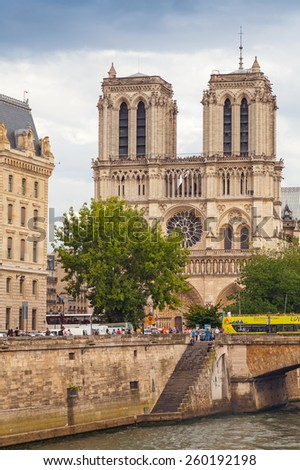 Paris, France - August 07, 2014: Vertical photo of Notre Dame de Paris cathedral. The most popular city landmark with people walking on Seine river embankment - stock photo