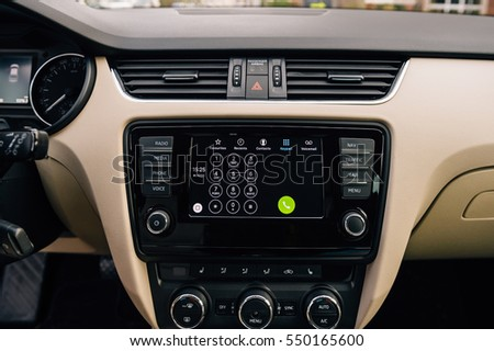 PARIS, FRANCE - DEC 13, 2016: Apple CarPlay phone main screen in modern car dashboard.  CarPlay is an Apple standard that enables a car radio to be a controller for an iPhone.