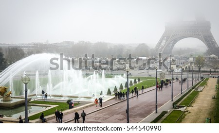PARIS, FRANCE - DEC 8, 2014: Early morning view of the Eiffel Tower in Paris, with the tower covered in fog.  The Eiffel Tower is one of Europe's most popular visitor attractions
