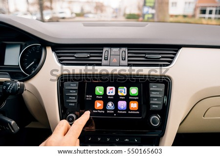 PARIS, FRANCE - DEC 13, 2016: Man pressing home button on the Apple CarPlay main screen in modern car dashboard. CarPlay is an Apple standard that enables a car radio to be a controller for an iPhone.