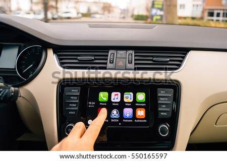 PARIS, FRANCE - DEC 13, 2016: Man pressing Now Playing button on the Apple CarPlay main screen in modern car dashboard.  CarPlay is an Apple standard that enables a car  controller for an iPhone.