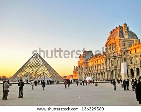PARIS, FRANCE-DEC. 24: The kings palace louvre with its famous pyramid on December 24, 2012. Louvre is the biggest Museum in Paris displayed over 60,000 sq.M. of exhibition space. - stock photo