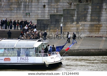 PARIS , FRANCE - DECEMBER 30: A crowd of people standing on the banks of the Seine next to a passenger ship on December 30, 2013 in Paris / Tour via Boat