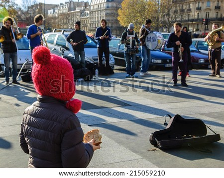 """PARIS, FRANCE - DECEMBER 8, 2013: Brass band performs and unidentified little girl  stands close to a cover with coins, holding slice of bread, creating by a chance """"Earning their bread"""" metaphor. - stock photo"""