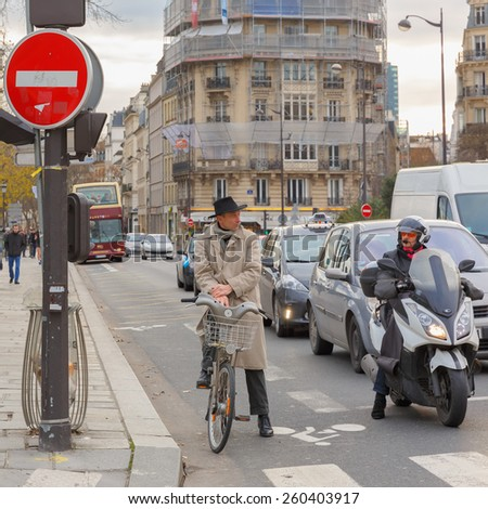 Paris, France - December 20, 2014: Cyclists and motorcyclists on a busy intersection in Paris waiting for the green light.