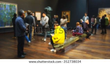 PARIS, FRANCE - DECEMBER 6, 2015: Defocused photo of visitors in permanent collection hall of Musee d'Orsay. Musee d'Orsay has the largest collection of impressionist paintings in the world. - stock photo