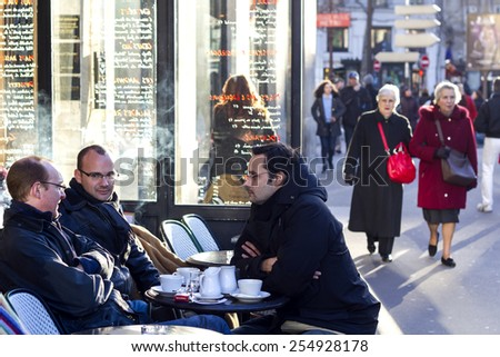 PARIS, FRANCE - DECEMBER 29 : Group of three men sitting over a table in the open french cafe in the central Paris with people walking on the street on the background on December 29th, 2013.  - stock photo