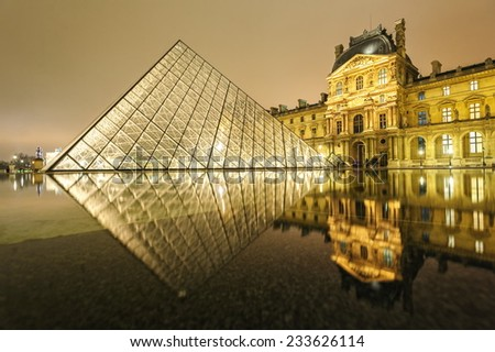 PARIS, FRANCE - DECEMBER 31: Louvre museum illuminated by night. With over 8 million visitors pro year is Louvre one of the world's largest museums. Paris, France on December 31, 2013  - stock photo