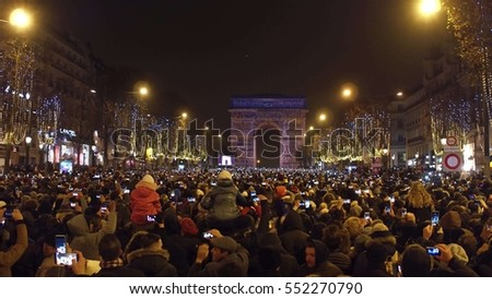 PARIS, FRANCE - DECEMBER, 31, 2016. Overhead shot of crowded Champs-Elysees street and light show on famous triumphal arch, Arc de Triomphe. New Year's eve