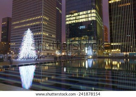 Paris, France - December 21, 2014: Stylized Christmas tree on the background of skyscrapers in Paris, La Defense.