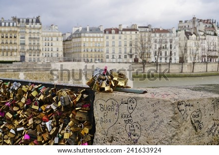 PARIS, FRANCE --DECEMBER 2014-- The city of Paris is locking down on the tourists' habit of attaching metal locks to the French capital's bridges to symbolize their eternal love.  - stock photo