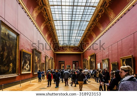PARIS, FRANCE - DECEMBER 22, 2014: Tourists visit art gallery in Louvre Museum. Louvre Museum is one of the largest and most visited museums worldwide.