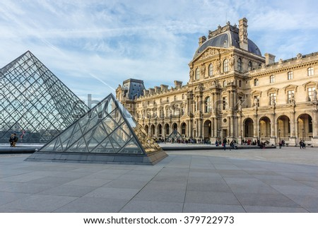 PARIS, FRANCE - DECEMBER 23, 2015: View Louvre building of Louvre Museum and Pyramid at sunset. Louvre Museum is one of the largest and most visited museums worldwide.