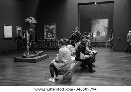 PARIS, FRANCE - DECEMBER 6, 2015: Visitors in permanent collection hall of Musee d'Orsay. Musee d'Orsay has the largest collection of impressionist and post-impressionist paintings in the world. - stock photo