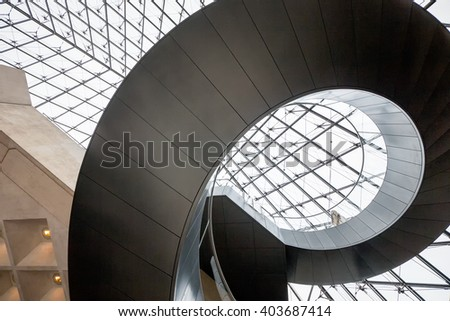 PARIS, FRANCE - FEB 14: Spiral staircase at Musee Louvre in Paris, France on February 14, 2013.  The iconic museum was designed by architect IM Pei. - stock photo