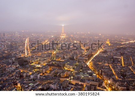PARIS, FRANCE - FEBRUARY, 13, 2016: Aerial view of Paris with Eiffel tower on the stormy rainy night in the winter season, with cloudy and fog.