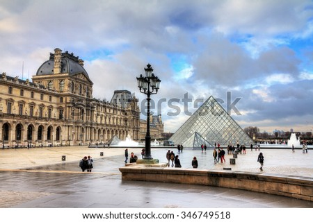 PARIS, FRANCE - FEBRUARY 19, 2014: Beautiful view of tourists visiting the Louvre museum in Paris, France, on a cloudy day in February, 2014 - stock photo