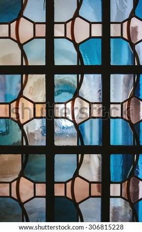 PARIS, FRANCE - FEBRUARY 10, 2015: Church corridor as seen through stained glass window with irregular block pattern in a hue of blue seen in Notre-Dame-de Paris Church - stock photo