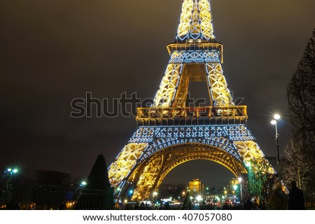 Paris, France - 11 February 2016: Eiffel Tower Middle Section Lights up with Twinkling White Lights at Night on Valentine's Day Weekend.