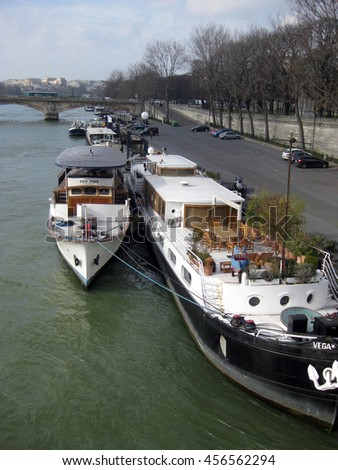 Paris, France - February 2015: View of Seine river and tourists anchored boats from the Pont Alexandre III.