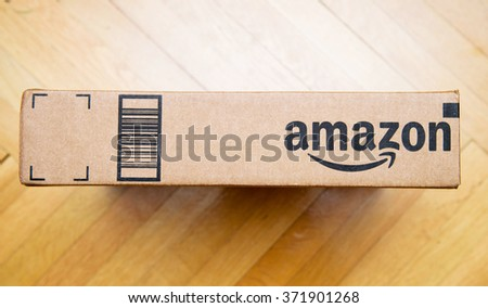 PARIS, FRANCE - JAN 28, 2016: Amazon logotype printed on cardboard box side seen from above on a wooden floor Amazon is the an American electronic e-commerce company - stock photo