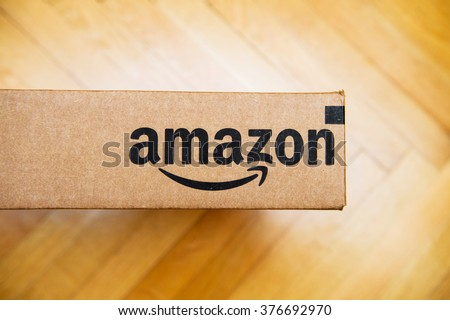 PARIS, FRANCE - JAN 28, 2016: Amazon logotype printed on cardboard box side, seen from above on a wooden floor. Amazon Inc is the an American electronic e-commerce company - stock photo